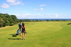 Camminare della ragazza del carrello e del giocatore di golf Fotografie Stock