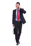 Camminare di andata mentre comunicando sul telefono Fotografia Stock