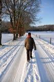 Camminare femminile maggiore attraverso la neve Immagini Stock
