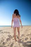 Camminare posteriore della donna sulla sabbia Fotografia Stock Libera da Diritti