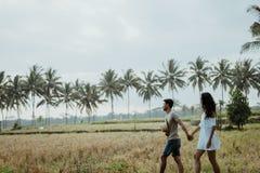 Camminata alla moda delle coppie nel giacimento del riso insieme fotografie stock
