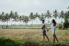 Camminata alla moda delle coppie nel giacimento del riso insieme immagini stock libere da diritti