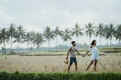 Camminata alla moda delle coppie nel giacimento del riso insieme fotografie stock libere da diritti