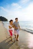 Camminata delle coppie lungo la spiaggia felicemente Immagine Stock