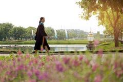 Camminata di laurea felice della donna asiatica con il sorriso grande Fotografie Stock Libere da Diritti