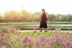 Camminata di laurea felice della donna asiatica con il sorriso grande Immagine Stock Libera da Diritti
