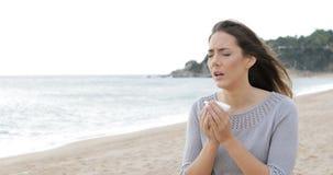 Camminata di starnuto della donna allergica sulla spiaggia video d archivio