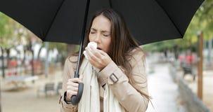 Camminata di starnuto della donna malata sotto la pioggia stock footage