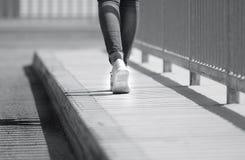 Camminata e passo avanti della donna con le scarpe ed i jeans all'aperto immagini stock