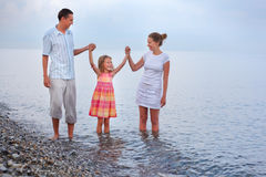 Camminata felice della famiglia sulla spiaggia, unente le mani Fotografia Stock