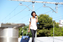 Camminata femminile afroamericana dalla stazione con la valigia ed il telefono cellulare Immagine Stock