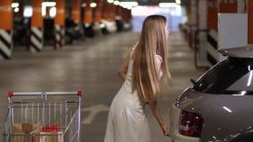 Camminata femminile con il carrello al tronco di automobile video d archivio