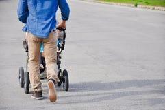 Camminata moderna dei pantaloni a vita bassa bei con il bambino in carrozzina all'aperto in città Fondo della strada con la destr Immagini Stock Libere da Diritti