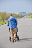 Camminata moderna dei pantaloni a vita bassa bei con il bambino in carrozzina all'aperto in città Foto verticale Fotografia Stock