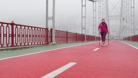 Camminata nordica Giovane donna caucasica paffuta che fa un'escursione con i pali nordici Front Static Shot video d archivio