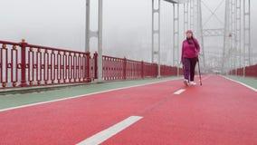 Camminata nordica Giovane donna caucasica paffuta che fa un'escursione con i pali nordici Front Static Shot Movimento lento archivi video