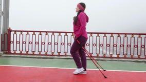 Camminata nordica Giovane donna caucasica paffuta che fa un'escursione con i pali nordici Il lato segue il colpo archivi video