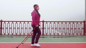 Camminata nordica Giovane donna caucasica paffuta che fa un'escursione con i pali nordici Il lato segue il colpo Movimento lento stock footage