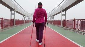 Camminata nordica Giovane donna caucasica paffuta che fa un'escursione con i pali nordici Indietro segua il colpo video d archivio
