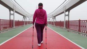 Camminata nordica Giovane donna caucasica paffuta che fa un'escursione con i pali nordici Indietro segua il colpo Movimento lento stock footage