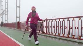 Camminata nordica Giovane donna caucasica paffuta che fa un'escursione con i pali nordici La facciata frontale segue il colpo Mov stock footage