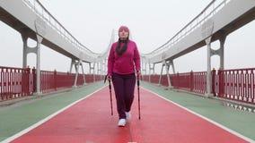 Camminata nordica Giovane donna caucasica paffuta che fa un'escursione con i pali nordici La parte anteriore segue il colpo Movim archivi video