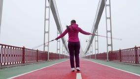 Camminata nordica Giovane donna caucasica paffuta che fa un'escursione con i pali nordici salto e ballare felici Colpo anteriore  video d archivio