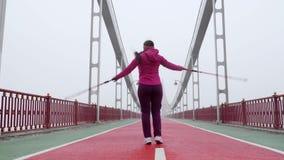 Camminata nordica Giovane donna caucasica paffuta che fa un'escursione con i pali nordici salto e ballare felici Colpo anteriore archivi video