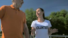 Camminata volontaria della femmina utile allegra con un uomo senior video d archivio