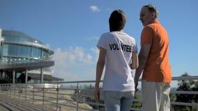 Camminata volontaria della femmina utile con un uomo senior archivi video