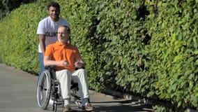 Camminata volontaria di indù utile con un uomo wheelchaired stock footage