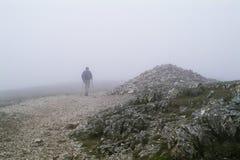 Camminatore solo in foschia dal cairn della montagna fotografia stock