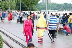 Camminatori di mattina, due culture differenti, fronte lago di Kankaria - India fotografie stock