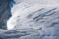 Camminatori fissati con le corde che attraversano ghiacciaio alpino di estate Fotografia Stock Libera da Diritti