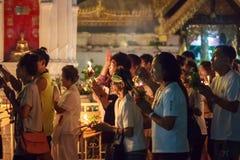 Cammini con le candele illuminate a disposizione intorno ad un tempiale Immagine Stock