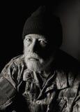 戴camo夹克和编织帽子的严肃的退伍军人 图库摄影