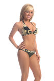Camo Bikini Blonde. Sexy blond swimwear model in a yellow and green camouflage bikini with her right hand on her hip Royalty Free Stock Photos