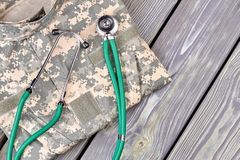 Camo clothes and medical stethoscope. Top view. Wooden desk background stock images