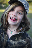 Camo and a silly face. A portrait of a cute dark haired little girl in a camo hat and coat making a silly face. Shallow depth of field Stock Photography