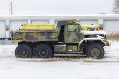 Camo truck. With flat tires surounded by snow stock photography