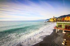 Camogli, Италия - люди ослабляя на пляже и базилике Santa Maria Assunta на заднем плане Стоковая Фотография RF