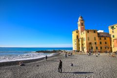 Camogli, Италия - люди ослабляя на пляже и базилике Santa Maria Assunta на заднем плане Стоковое Изображение