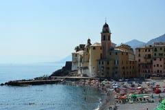 CAMOGLI, ITALY - JUNE 13, 2017: tourists on the beach with Basilica of Santa Maria Assunta on the background, Camogli, Liguria Royalty Free Stock Photo