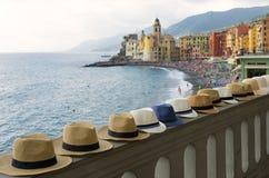 Camogli tourist;some hats for sale frame a beautiful Camogli, Liguria, Italy royalty free stock image