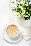 Camomile hebal tea in a white cup with Royalty Free Stock Photos