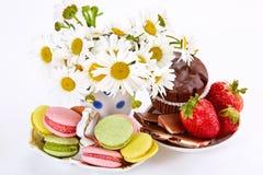 Camomiles en florero, macarrones en el platillo con la fresa y choco Fotografía de archivo