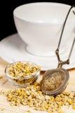 Camomille sèche avec le paraboloïde de tamis et en verre de thé image stock