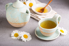 Camomille tea in handmade ceramic cup. Hot camomille tea with honey in handmade ceramic cup royalty free stock photography