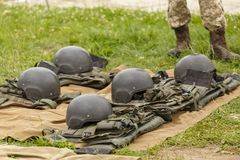 Camouflage combat flak jackets and helmets lined up on the ground stock images