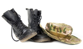 Camouflage hat resting on a pair of combat boots. Royalty Free Stock Images